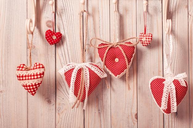 Красные сердечки, висящие на крючках. поздравление с рождеством или дня святого валентина