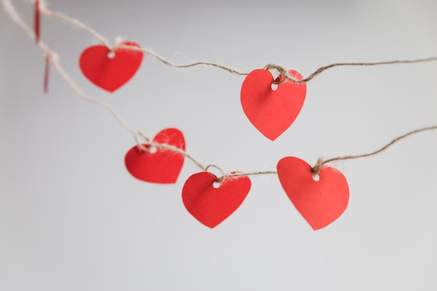 Red hearts hanging on ropes