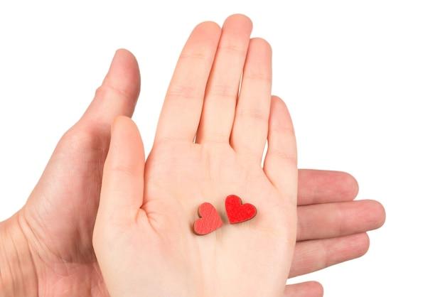 Красные сердца в руках пары, изолированные на белом. скопируйте пространство.