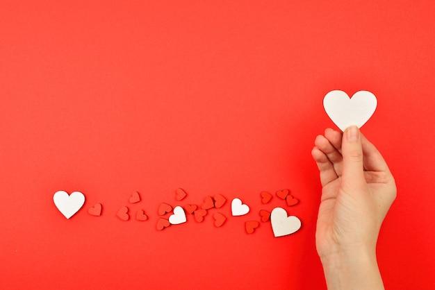 Красные сердца в руке женщины на красном фоне копией пространства