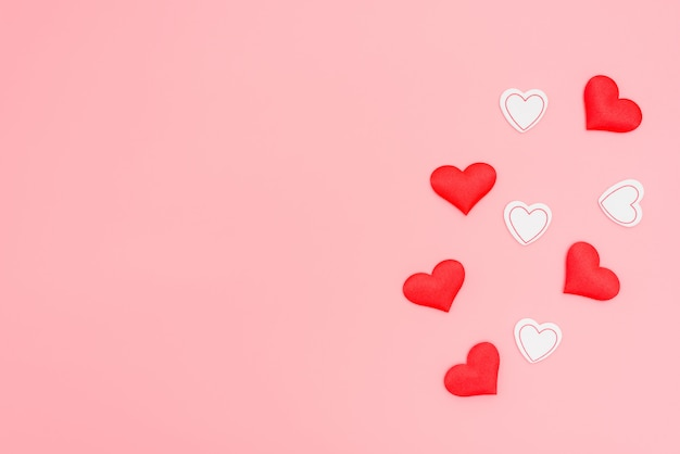 Red hearts of love on a pink flat background