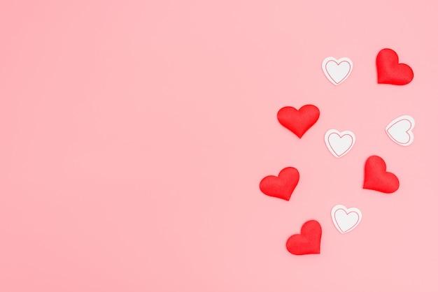 Красные сердца любви на розовом плоском фоне