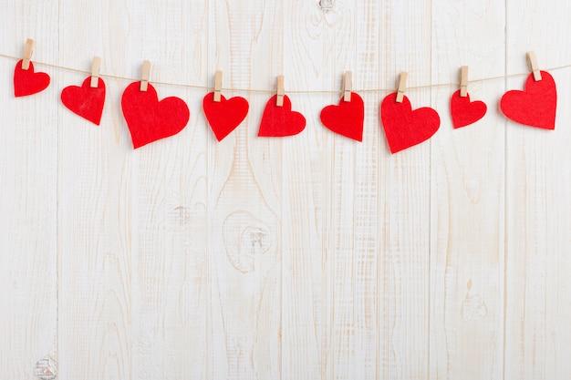 흰색 나무 배경에 clothespins와 밧줄에 빨간 하트