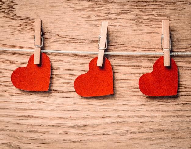 Красные сердца на прищепках на деревянных фоне. фото с копией пространства