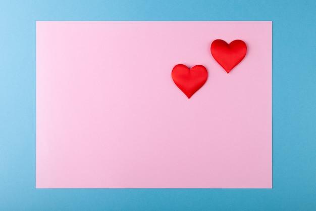 色付きの背景に赤いハート、青いフレームのピンク、バレンタインデーのグリーティングカードのコンセプト