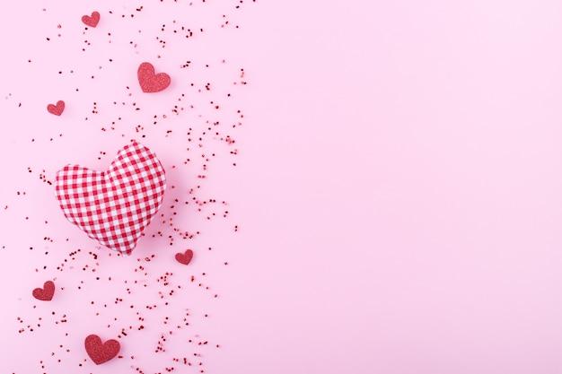 Красные сердечки на розовом фоне Premium Фотографии