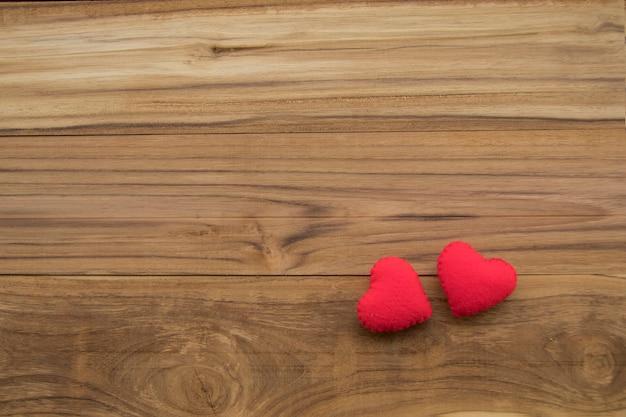 バレンタインメッセージのコピースペースを持つ木製の背景に赤いハート