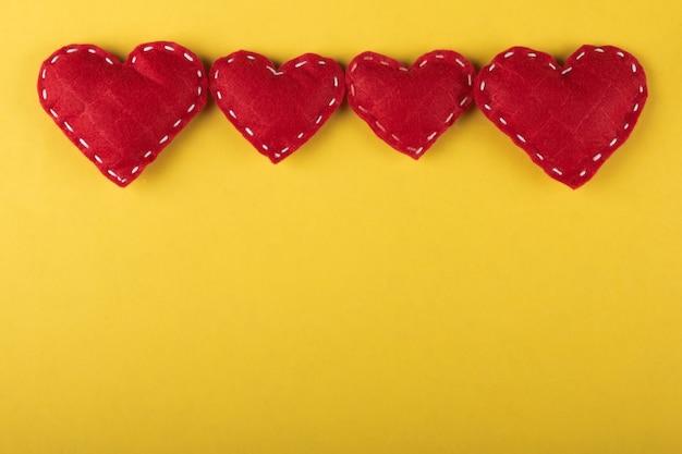 Красные сердца на желтом фоне.