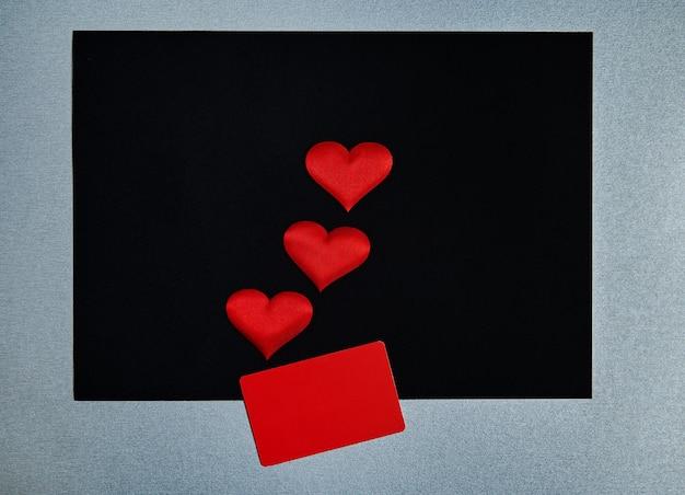 Красные сердечки, красный прямоугольник на черном / сером фоне. концепция дня святого валентина. граница, копия пространства, вид сверху, праздник, праздник