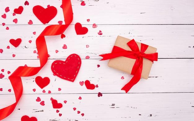 赤いハート、リボン、白い木製の背景にギフト。上面図、テキスト用の空き領域。バレンタインデー、愛。
