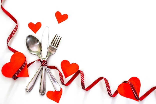 Red hearts, ribbons and cutlery