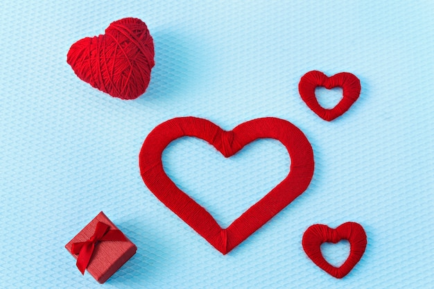 Red hearts and ring on a blue background