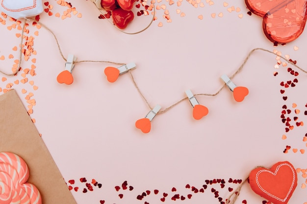 Red hearts on a rope with beads, on a white wooden background. space for text, space for copying.