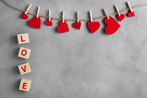 Red hearts on rope with clothespins, on a white grey concrete background. cubes with the word love. place for text, copy space.