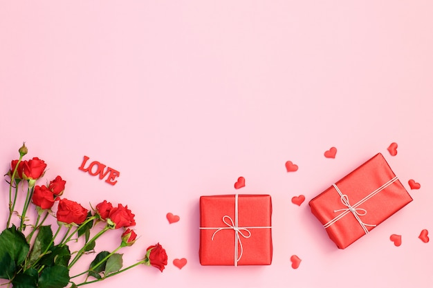 Red hearts, rose and gift box on pink background