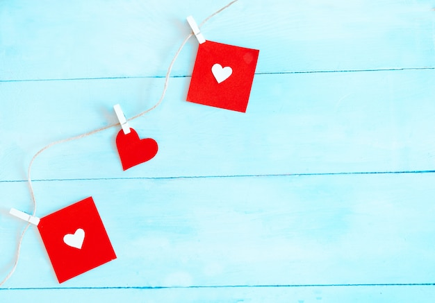 Red hearts set on string over blue background. valentine's day concept.
