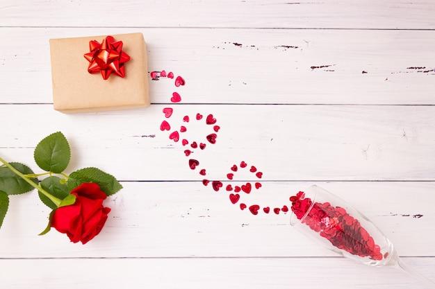 Красные сердечки выливаются из бокала шампанского, подарочной коробки и розы