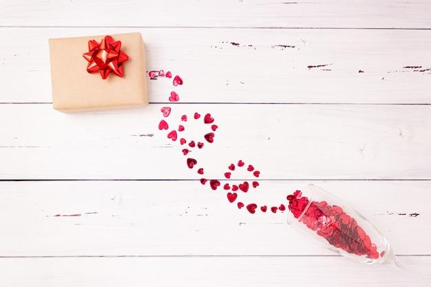 Красные сердечки выливаются из бокала шампанского и подарочной коробки