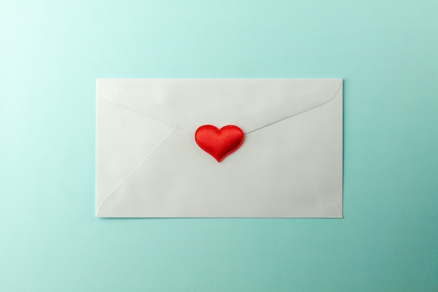 Red hearts stamped at white envelope on blue paper background