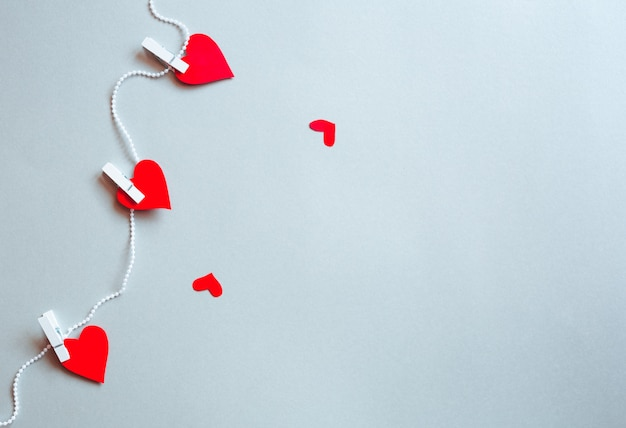 Red hearts stuck with pliers on a ribbon. valentine's day concept