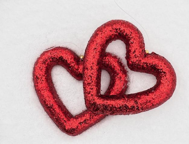 Игрушка красные сердца на фоне снега