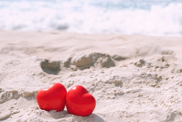 Red hearts on tropical beach in sunny day