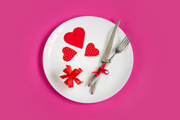 Red hearts on a white plate, a fork, a knife, a gift box on pink