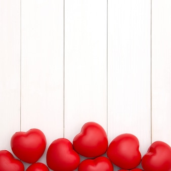 Red hearts on white wooden background with copy space for valentine's day. love concept. minimal style.