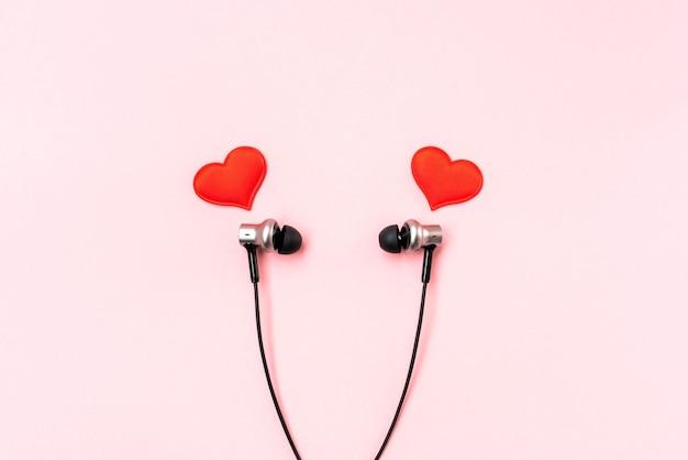 Красные сердца с черными музыкальными наушниками на розовой пастели.
