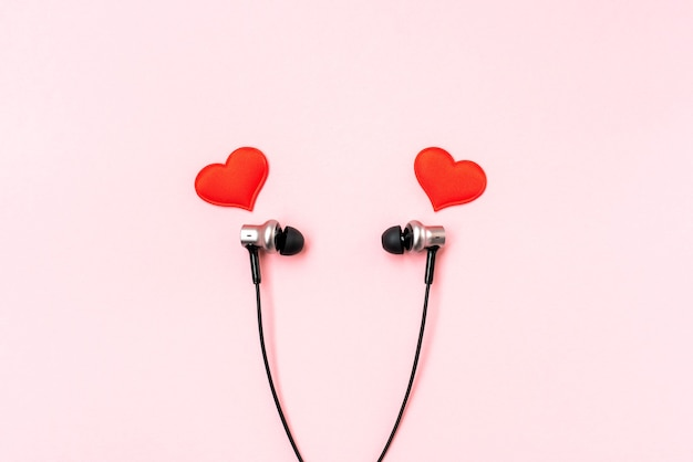 Red hearts with black music earphones on pink pastel.