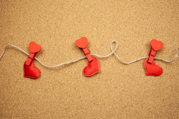 Red hearts with clothespins on corkboard, strong love concept