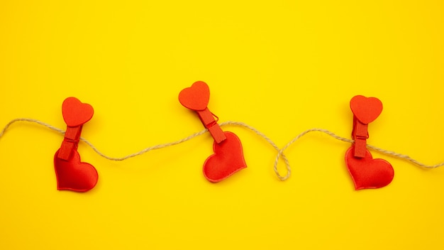 Red hearts with clothespins on yellow background, strong love concept