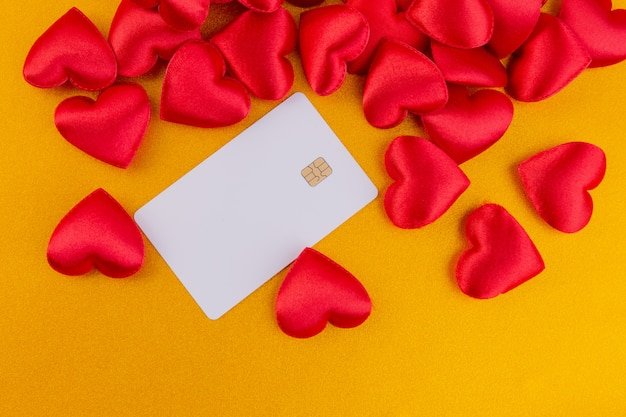 Red hearts with credit card on glitter color gold, valentines day background