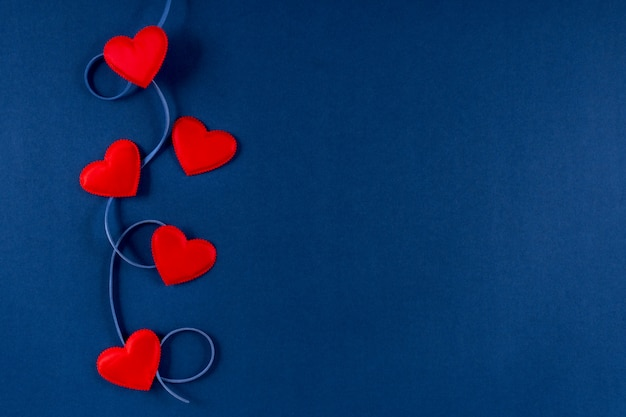 Red hearts with ribbon on classic blue 2020 color background. valentines day 14 february concept. flat lay, copy space, top view, banner.