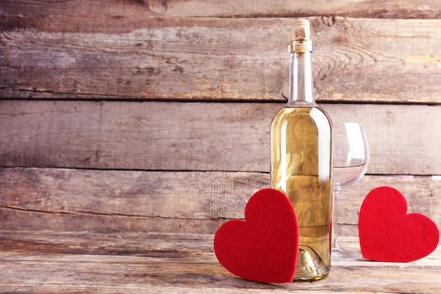 木製の壁にワインボトルとグラスと赤いハート