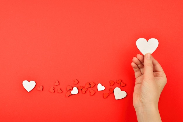 Red hearts in woman hand on a red background copy space
