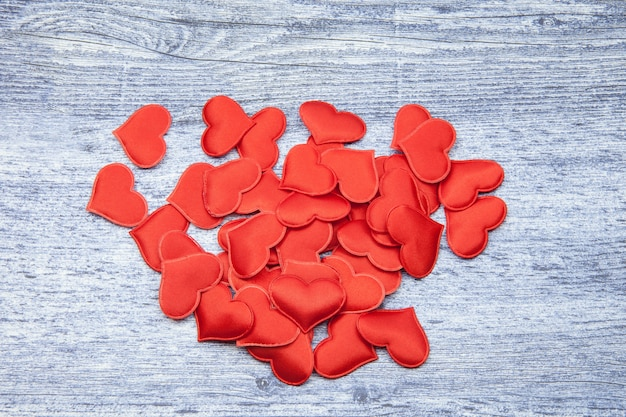 Red hearts on a wooden jeans color background, concept of love and loyalty