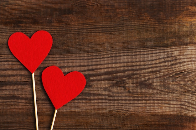 Red hearts on a wooden table.