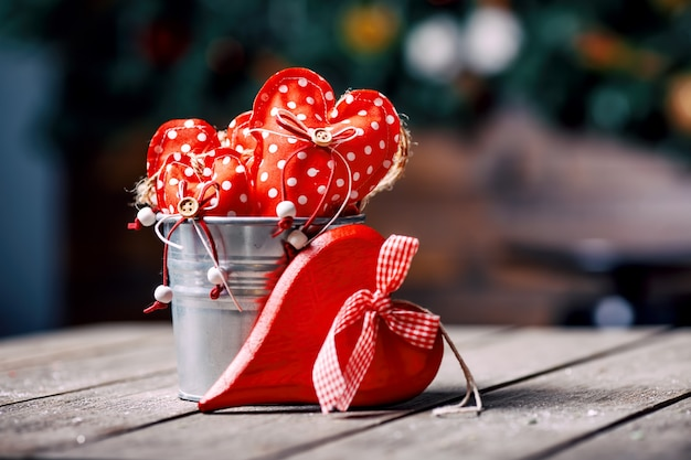 Red hearts in zinc bucket on wooden background in vintage and retro style. valentine concept.