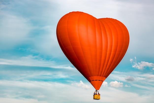 Красный шар в форме сердца на фоне неба с облаками - подарок на день святого валентина