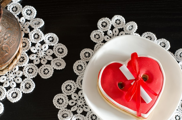 Red heartshaped gingerbread with a message on a white plate