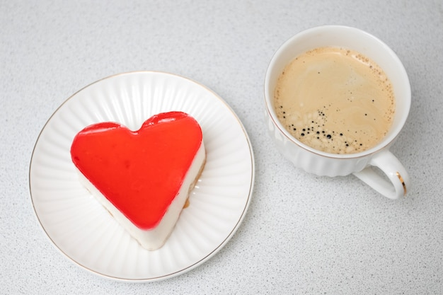 Red heat shaped cake for st. valentines day celebration with cup of coffee