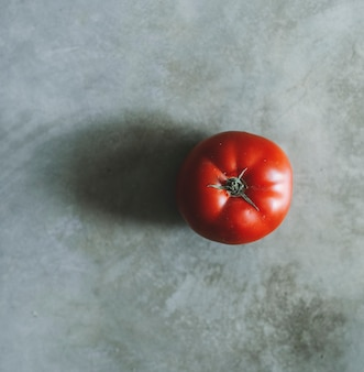 Red heirloom tomato on a gray background