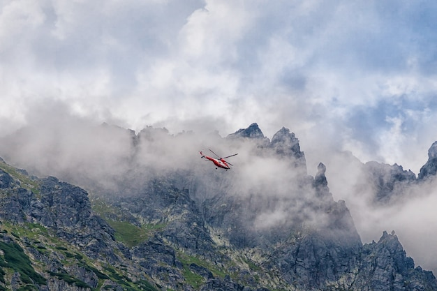 Red helicopter flying over the mountains tatra, poland.