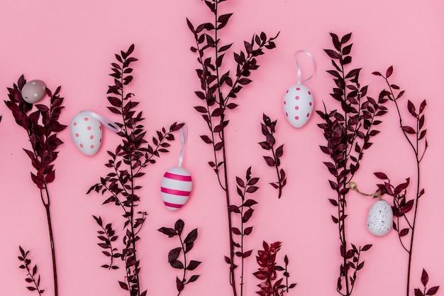 레드 허브 가지와 분홍색 배경에 부활절 달걀. 보기 위