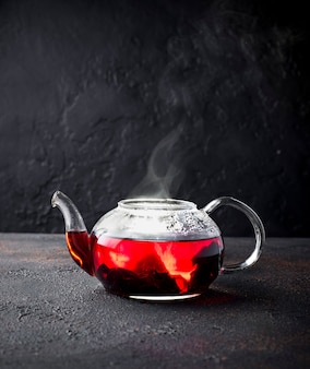 Red hibiscus flower tea in glass teapot