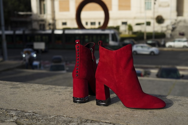 Red high heel boot with city background