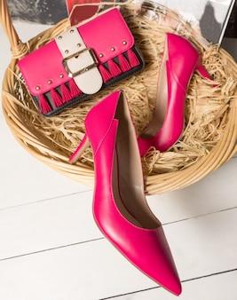 バスケットにハンドバッグが入った赤いハイヒールの靴