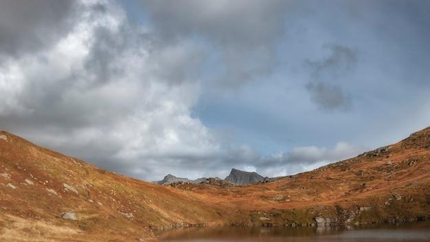 붉은 언덕, 산, 구름이 있는 푸른 하늘, 북극 노르웨이의 로포텐 섬의 아름다운 가을