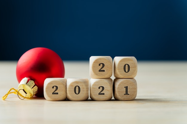 Red holiday bauble next to a 2021 sign on wooden dices with number 20 on top.